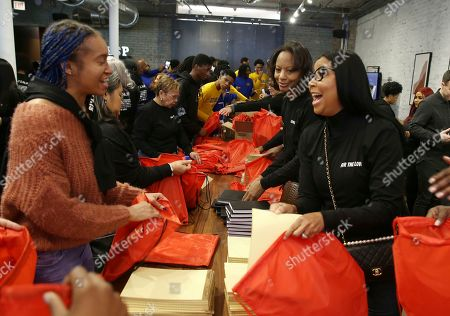 Stock Image of Melanye Reid, Cookie Johnson. NBWA Vice-President and Director Cookie Johnson right and Melanye Reid are seen packing care kits at the NBWA NBA All-Star Weekend Community Love Fest presented by Toyota on in Chicago
