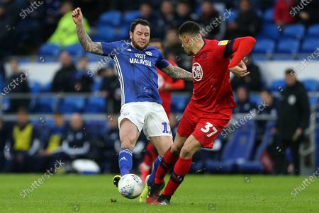Lee Tomlin of Cardiff City is tackled by Leon Balogun of Wigan.