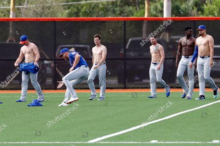 New York Mets pitcher Noah Syndergaard (34) runs past teammates to gather up their jerseys after they warmed up without them during spring training baseball practice, in Port St. Lucie, Fla. The players warmed up without their jerseys to poke fun at Syndergaard who was recently spotted working out shirtless