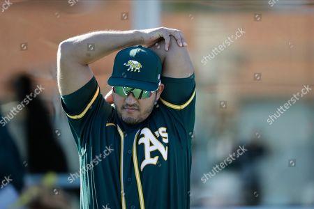 Oakland Athletics' Carlos Perez stretches during spring training baseball practice, in Mesa, Ariz