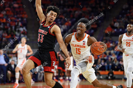 Clemson's John Newman lll (15) drives against Jordan Mwora during the first half of an NCAA college basketball game, in Clemson, S.C