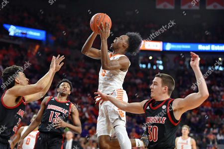 Clemson's John Newman lll (15) drives to the basket as Louisville's Jordan Nwora, left, David Johnson, center, and Ryan McMahon defend during the first half of an NCAA college basketball game, in Clemson, S.C. Clemson won 77-62