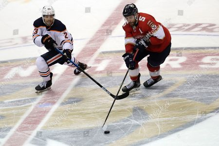 Edmonton Oilers center Riley Sheahan (23) and Florida Panthers defenseman Aaron Ekblad (5) go for the puck during the third period of an NHL hockey game, in Sunrise, Fla. The Oilers won 4-1