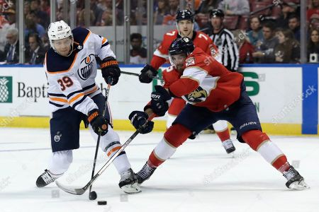 Edmonton Oilers right wing Alex Chiasson (39) and Florida Panthers defenseman Aaron Ekblad (5) go for the puck during the second period of an NHL hockey game, in Sunrise, Fla