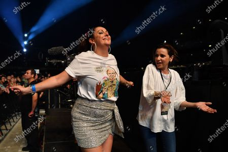 Stock Photo of Celeste Barber (L) wearing a shirt featuring Prime Minister Scott Morrison and Tina Arena dance along to John Farnham during the Fire Fight Australia bushfire relief concert at ANZ Stadium in Sydney, Australia, 16 February 2020. Thousands of people attended the concert, with 10 hours of musical performances, to raise funds for communities devastated by bushfires.