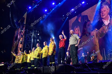 Firefighters join John Farnham (lL) and Olivia Newton-John on stage as they perform during the Fire Fight Australia bushfire relief concert at ANZ Stadium in Sydney, Australia, 16 February 2020. Thousands of people attended the concert, with 10 hours of musical performances, to raise funds for communities devastated by bushfires.