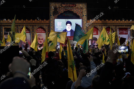 Hezbollah leader Sayyed Hassan Nasrallah speaks via video link during a ceremony marking the anniversary of the assassination of Hezbollah leaders, Abbas al-Moussawi, Ragheb Harb and Imad Mughniyeh and the end of a 40-day Muslim mourning period for slain Iranian Revolutionary Guard Gen. Qassem Soleimani, in the southern suburb of Beirut, Lebanon, . Nasrallah said U.S. President Donald Trump declared war on the Middle East when the U.S. assassinated Soleimani and when the White House announced its plan to end the Palestinian-Israeli conflict. He called on all to resist U.S. influence and its troops presence