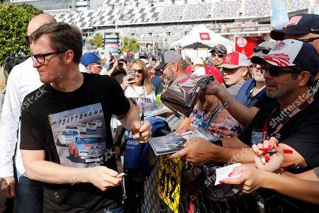 Dale Earnhardt Jr., team owner and TV analyst signs autographs outside the media center before the NASCAR Daytona 500 auto race at Daytona International Speedway, in Daytona Beach, Fla