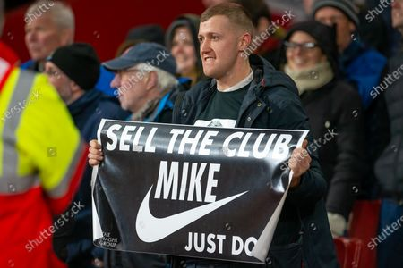 Unhappy Newcastle fan holds banner suggesting Mike Ashley should sell the club