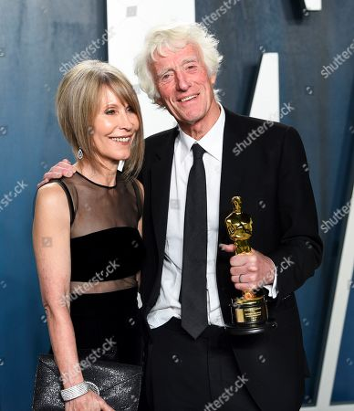 "James Ellis, Roger Deakins. Roger Deakins, winner of the award for best cinematography for ""1917"", poses with his wife James Ellis at the Vanity Fair Oscar Party, in Beverly Hills, Calif"
