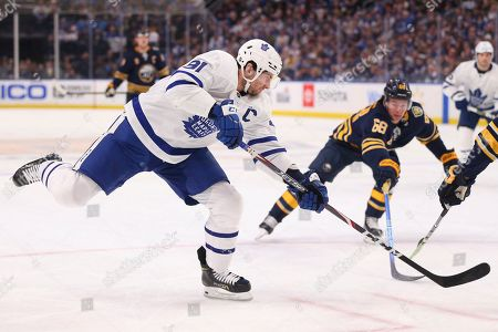 Toronto Maple Leafs forward John Tavares shoots during the first period of the team's NHL hockey game against the Buffalo Sabres, in Buffalo, N.Y