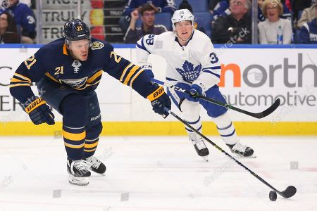 Buffalo Sabres forward Kyle Okposo (21) carries the puck past Toronto Maple Leafs defenseman Rasmus Sandin (38) during the third period of an NHL hockey game, in Buffalo, N.Y