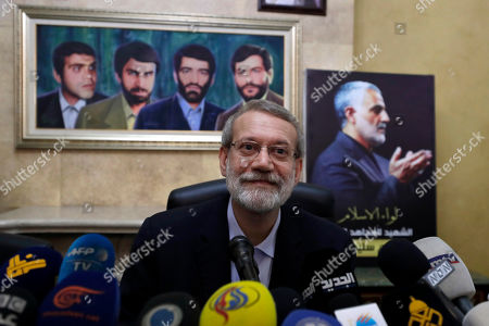 Iranian Parliament Speaker Ali Larijani, gives a press conference, in front of a painting of four missing Iranian diplomats who disappeared during the 1982 Israeli invasion of Lebanon, left, and a picture of the late Iranian Quds Force top commander Qassem Soleimani, right, at the Iranian Embassy in Beirut, Lebanon