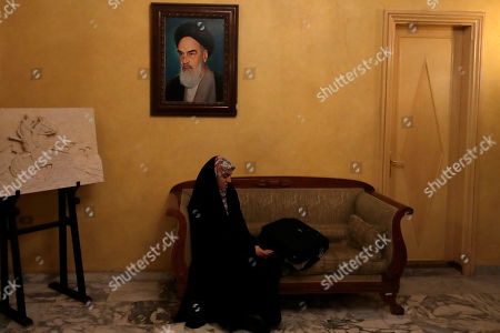 An Iranian official listens as Iranian Parliament Speaker Ali Larijani gives a press conference at the Iranian Embassy in Beirut, Lebanon, . The picture shows the late revolutionary founder Ayatollah Khomeini