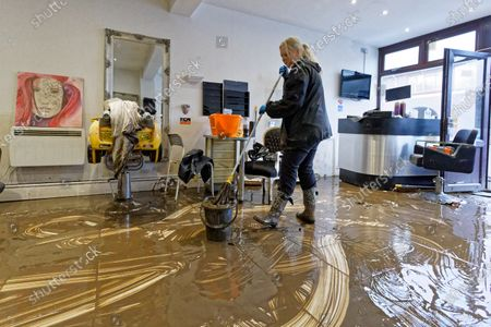 Stock Photo of Louise Bedgood mops up the floor of Lougos hair dressers in Oxford Street, Nantgarw, Wales, Britain, 17 February 2020. Storm Dennis hit the region over the past weekend bringing torrential rains, floods and landslides.