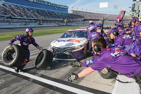 Denny Hamlin's crew changes tires and refuels during a pit stop during the NASCAR Daytona 500 auto race at Daytona International Speedway, in Daytona Beach, Fla. Sunday's race was postponed sue to rain