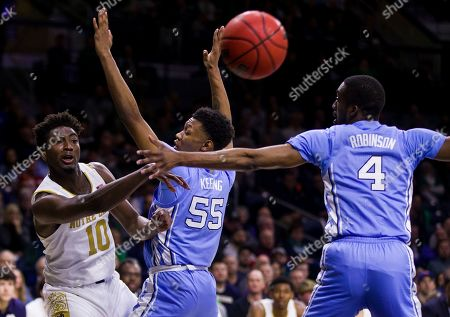 Notre Dame's Temple 'T.J.' Gibbs (10) passes around North Carolina's Christian Keeling (55) and Brandon Robinson (4) during the second half of an NCAA college basketball game, in South Bend, Ind. Notre Dame won 77-76