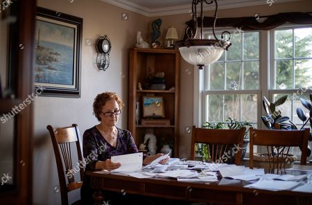 "Janet Uhlar sits at her dining room table with letters and photos she received through her correspondence with imprisoned Boston organized crime boss James ""Whitey"" Bulger, in Eastham, Mass. Although much had been written about the CIA's mind control experiments before Bulger's trial, Uhlar said she knew nothing about them until she began corresponding with the renowned gangster following his conviction in the fall of 2013"