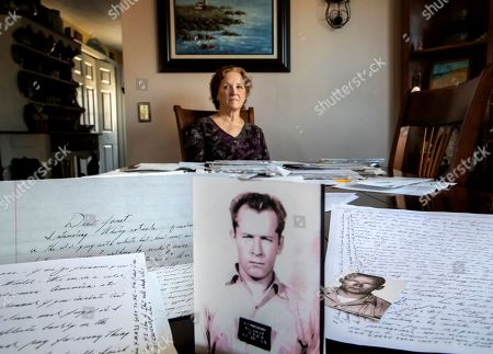 "Janet Uhlar sits for a photo at her dining room table with an arrangement of letters and pictures she received through her correspondence with imprisoned Boston organized crime boss James ""Whitey"" Bulger, in Eastham, Mass. Uhlar was one of 12 jurors who found Bulger guilty in a massive racketeering case, including involvement in 11 murders. But now she says she regrets voting to convict Bulger on the murder charges, because she learned he was an unwitting participant in a secret CIA experiment in which he was dosed with LSD on a regular basis for 15 months"