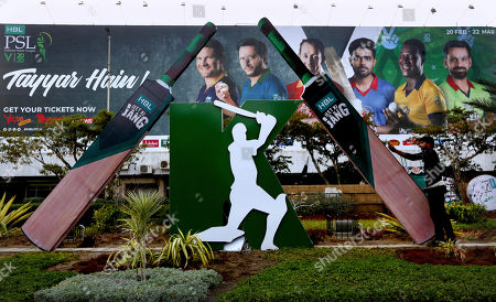 A worker install a cut-out of huge bats next to a poster of cricketers displays along roadside in preparation of the upcoming Pakistan Super League, in Karachi, Pakistan. Security concerns stopped foreign cricketers from touring Pakistan four years ago when the country's premier domestic Twenty20 tournament was launched, forcing organizers to stage the event on neutral turf in the United Arab Emirates. When the 2020 edition of the PSL starts in Karachi on Thursday, Darren Sammy of the West Indies and Shane Watson of Australia will be among 36 foreign cricketers involved in the six franchises
