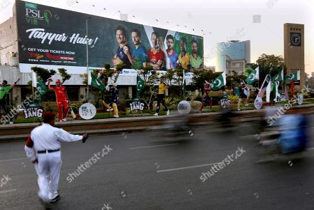 A traffic police officer control traffic infant of huge billboard of cricketers displays along roadside in preparation of the upcoming Pakistan Super League, in Karachi, Pakistan. Security concerns stopped foreign cricketers from touring Pakistan four years ago when the country's premier domestic Twenty20 tournament was launched, forcing organizers to stage the event on neutral turf in the United Arab Emirates. When the 2020 edition of the PSL starts in Karachi on Thursday, Darren Sammy of the West Indies and Shane Watson of Australia will be among 36 foreign cricketers involved in the six franchises