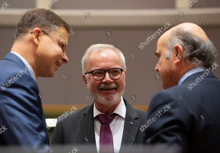 European Commissioner for An Economy that Works for People Valdis Dombrovskis, left, speaks with European Central Bank Vice-President Luis de Guindos, right, and President of the European Investment Bank Werner Hoyer during a meeting of EU finance ministers at the Europa building in Brussels, . EU finance ministers meet Tuesday to discuss tax havens