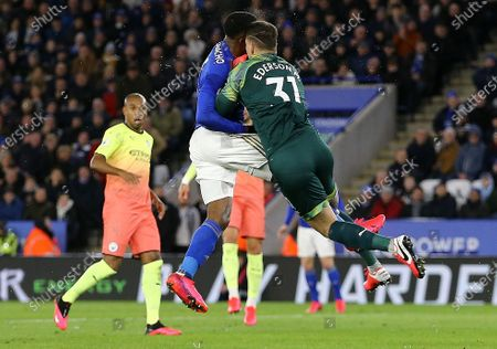 Ederson Moraes of Manchester City clashes heads with Kelechi Iheanacho of Leicester City