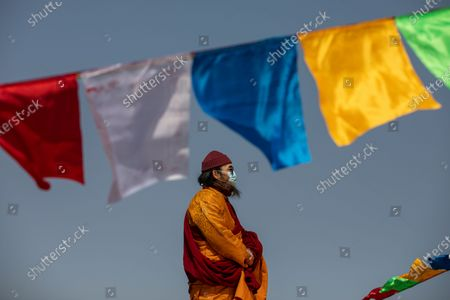 Stock Photo of Ngawang Kunga Tenzin Gyatso Rinpoche sets up prayer flags at the start of a Buddha Sunning Festival in Tai Mo Shan, Hong Kong, China, 18 February 2020. Rinpoche led a prayer and offered blessings to Hong Kong as the city deals with the novel coronavirus that causes the disease known as Covid-19. As of 18 February a total of 61 people were infected in Hong Kong, while in mainland China the number of cases leapt to more than 72,000 and the death toll was at least 1,860.