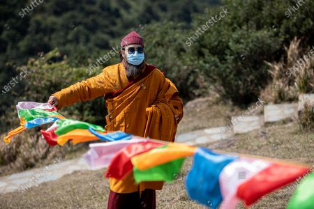 Ngawang Kunga Tenzin Gyatso Rinpoche sets up prayer flags at the start of a Buddha Sunning Festival in Tai Mo Shan, Hong Kong, China, 18 February 2020. Rinpoche led a prayer and offered blessings to Hong Kong as the city deals with the novel coronavirus that causes the disease known as Covid-19. As of 18 February a total of 61 people were infected in Hong Kong, while in mainland China the number of cases leapt to more than 72,000 and the death toll was at least 1,860.
