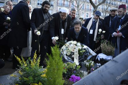 Imam Hassen Chalghoumi (C-L) and French author Marek Halter (3-L) place flowers with a group of Imams from Europe in front of the entrance the Bataclan concert venue during a tribute for victims of the November 2015 Paris attacks, in which 130 people were killed, in Paris, France, 18 February 2020.
