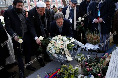 French author Marek Halter, Imam Hassen Chalghoumi, and French former lawmaker Georges Fenech lay flowers with a group of Imams from Europe in front of the Bataclan concert hall during a tribute for victims of the November 2015 Paris attacks in which130 people were killed, in Paris, . Chalghoumi launches the first European Conference of Imams Against Radicalization until Thursday Feb 20