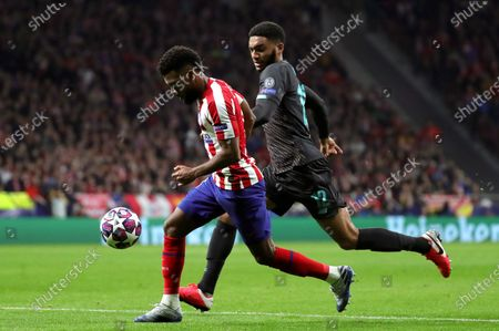 Atletico's winger Thomas Lemar (L) vies for the ball against Liverpool's defender Joe Gomez (R) during the UEFA Champions League round of 16 first leg match between Atletico de Madrid and Liverpool FC at Wanda Metropolitano in Madrid, Spain, 18 February 2020.