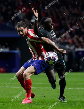 Liverpool's Sadio Mane, left, and Atletico Madrid's Sime Vrsaljko fight for the ball during a 1st leg, round of 16, of the Champions League soccer match between Atletico Madrid and Liverpool at the Wanda Metropolitano stadium in Madrid