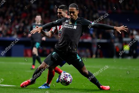 Liverpool's Virgil van Dijk, foreground, controls the ball past Atletico Madrid's Sime Vrsaljko during a 1st leg, round of 16, of the Champions League soccer match between Atletico Madrid and Liverpool at the Wanda Metropolitano stadium in Madrid