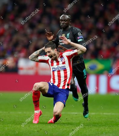 Liverpool's Sadio Mane, left, stops Atletico Madrid's Sime Vrsaljko during a 1st leg, round of 16, of the Champions League soccer match between Atletico Madrid and Liverpool at the Wanda Metropolitano stadium in Madrid