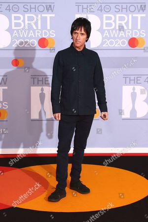Johnny Marr poses for photographers upon arrival at the Brit Awards 2020 in London