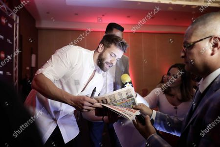 Pablo Alboran (L) signs autographs during a press conference in San Jose, Costa Rica, 18 February 2020. Alboran said that Latin America is a source of inspiration and a key to his artistic career.