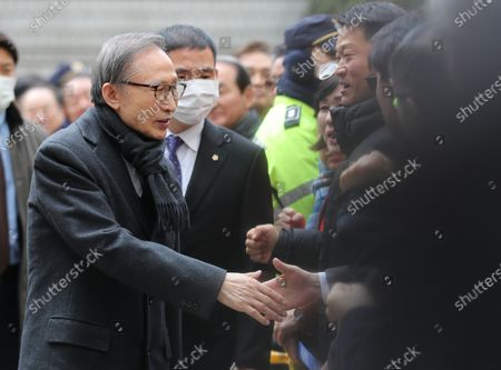 Former President Lee Myung-bak (L) shakes hands with his supporters after arriving at the Seoul High Court in Seoul, South Korea,  19 February 2020, to attend his trial. Lee, who was freed on bail from a detention center on 06 March, is appealing a 15-year sentence for bribery, embezzlement and other acts of corruption.