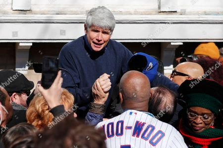Former Illinois Gov. Rod Blagojevich acknowledges Chicago Cubs' fam Ronnie Woo Woo after a news conference outside his home, in Chicago. On Tuesday, President Donald Trump commuted Blagojevich's 14-year prison sentence for political corruption