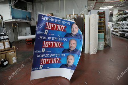 Israeli workers hold an election banner of Yisrael Beiteinu party leader Avigdor Lieberman, in a printing plant in Petah Tikva, Israel, 19 February 2020. Israel will head to the polls on 02 March 2020 to elect the Knesset members in the third general elections in a year.