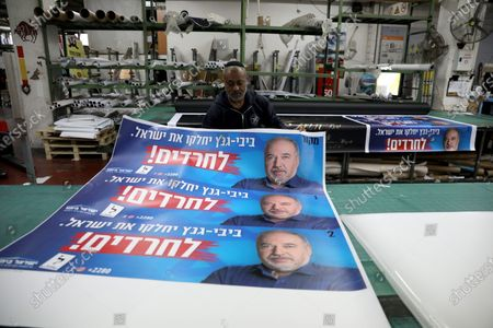 Israeli workers hold an election banner of Avigdor Lieberman, leader of the Israel Beitenu Party at a printing house, in Petah Tikva, Israel, 19 February 2020. Israel will go to general elections on 02 March.