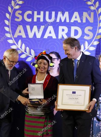 Stock Picture of EU Ambassador to Myanmar Kristian Schmidt (R) gives Schuman Awards to Women's Rights activist Lway Poe Ngeal (C) from Women's League of Burma during Schuman Awards ceremony at the EU Ambassador residence in Yangon, Myanmar, 19 February 2020. The European Union in Myanmar gives the annual Schuman Awards to recognize outstanding merits in the promotion of universal values of democracy, rule of law, peace and human rights. Human rights Lawyer Kyee Myint, Women's Rights activist Lway Poe Ngeal from Women's League of Burma and The Peacock Generation Thangyat (The satirical poet group) are the recipients of this year's 2020 Schuman Awards.