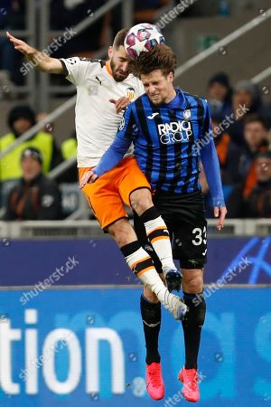 Valencia's Eliaquim Mangala, left, jumps for a header with Atalanta's Hans Hateboer during the Champions League round of 16, first leg, soccer match between Atalanta and Valencia at the San Siro stadium in Milan, Italy