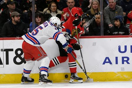 Chicago Blackhawks' Patrick Kane (88) battles New York Rangers' Ryan Lindgren (55) for a loose puck during the second period of an NHL hockey game, in Chicago