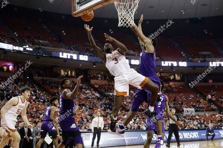 Courtney Ramey, Kevin Samuel. Texas guard Courtney Ramey (3) drives to the basket against TCU center Kevin Samuel (21) during the second half of an NCAA college basketball game in Austin, Texas