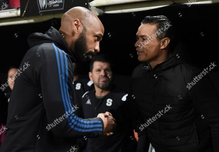 Canada's Montreal Impact head coach Thierry Henry, left, shakes hands with Costa Rica's Deportivo Saprissa head coach Walter Centeno prior a CONCAFAF Champions League soccer match at the Ricardo Saprissa Stadium in San Jose, Costa Rica