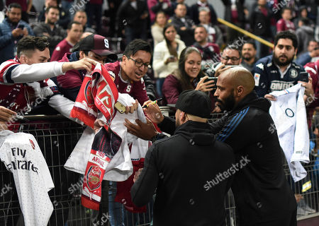 Canada's Montreal Impact head coach Thierry Henry, right, signs soccer jerseys prior a a CONCAFAF Champions League soccer match against Costa Rica's Deportivo Saprissa at the Ricardo Saprissa Stadium in San Jose, Costa Rica