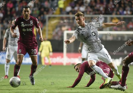 Stock Photo of Amar Sejdic of Canada's Montreal Impact, right, avoids a tackle by midfielder David Guzman of Costa Rica's Deportivo Saprissa during a CONCAFAF Champions League soccer match at the Ricardo Saprissa Stadium in San Jose, Costa Rica
