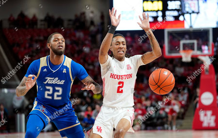 Houston's Caleb Mills (2) loses the ball as Tulsa's Reggie Jones (22) defends during the first half of an NCAA college basketball game, in Houston