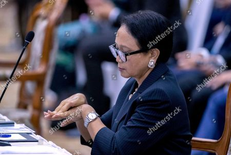 Indonesia's Foreign Minister Retno Marsudi cleans her hands with a disinfection ahead of the Special Meeting of Foreign ministers of The Association of Southeast Asian Nations (ASEAN) coordination council in Vientiane, Laos